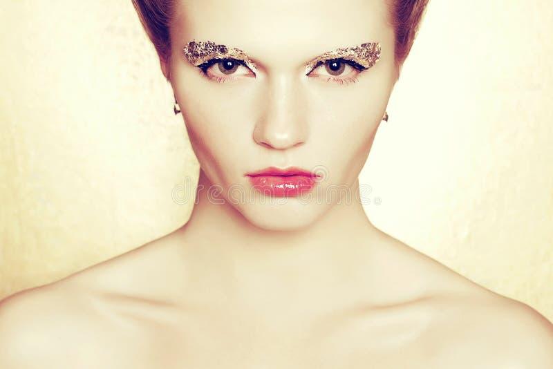 Porträt eines modernen Modells mit dem Artymake-up der goldenen Folie aufwerfend über goldenem Hintergrund H?bsches M?dchen in de lizenzfreie stockfotos