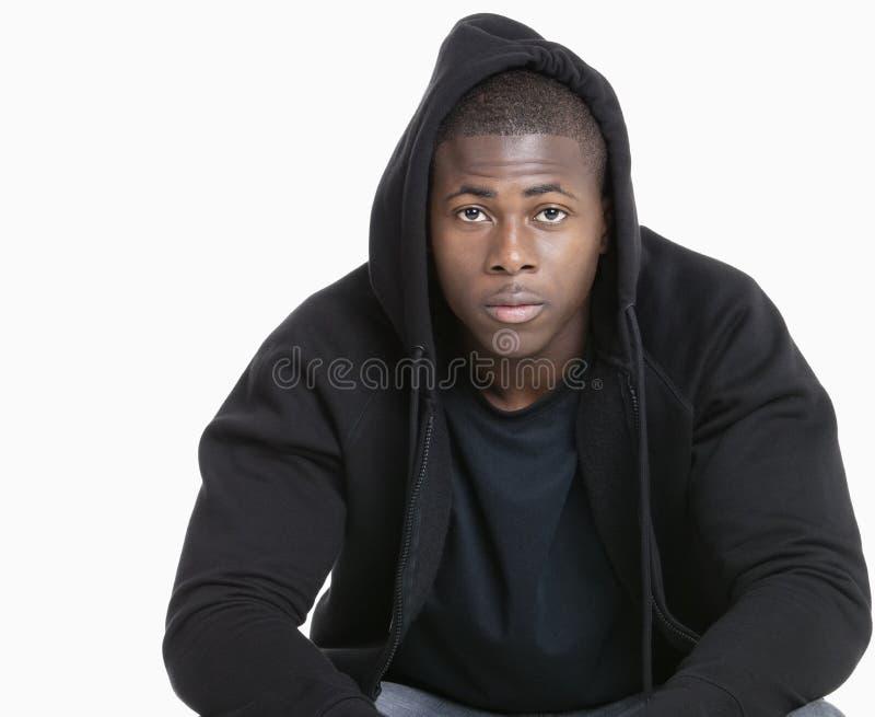 Porträt eines modischen Afroamerikanermannes, der mit Kapuze Sweatshirt über grauem Hintergrund trägt stockfotos