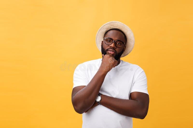 Porträt eines nachdenklichen afroen-amerikanisch Mannes in den Gläsern, die oben dem copyspace lokalisiert auf einem gelben Hinte stockfoto