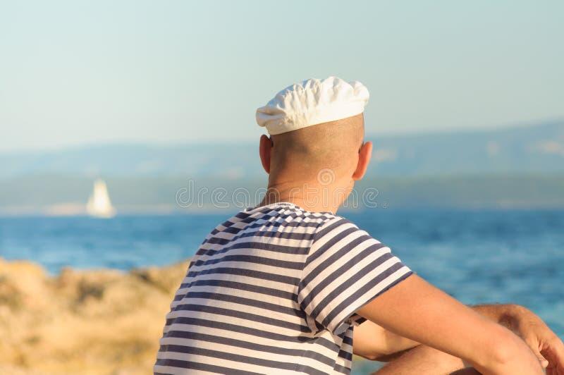 Porträt eines nachdenklichen jungen Mannes mit einem Hut, der durch das Meer in der Sommerzeit sitzt lizenzfreie stockbilder