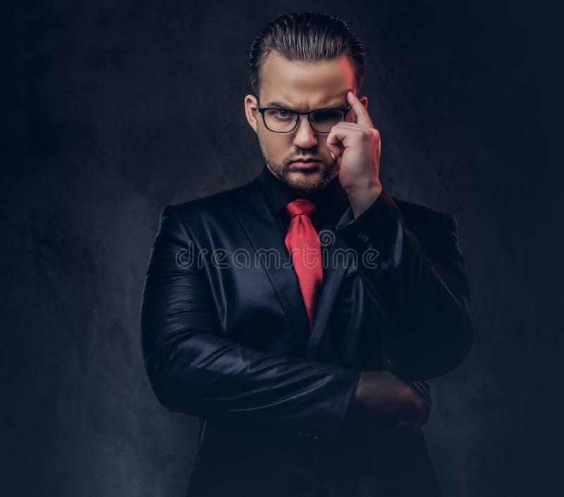 Porträt eines nachdenklichen stilvollen Mannes in einem schwarzen Anzug und in einer roten Bindung lizenzfreies stockbild