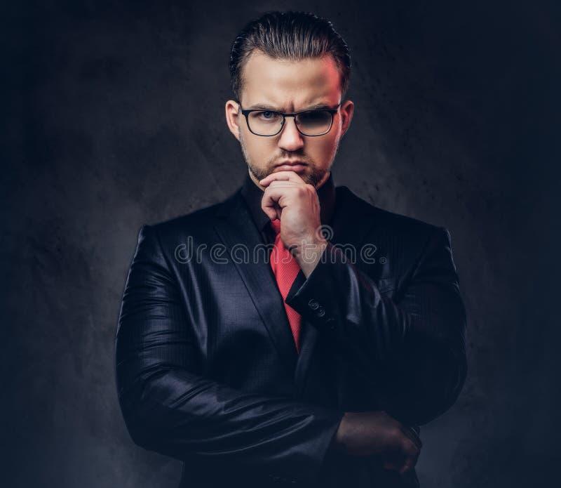 Porträt eines nachdenklichen stilvollen Mannes in einem schwarzen Anzug und in einer roten Bindung stockfoto