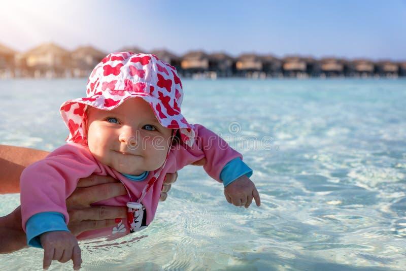 Portr?t eines netten Babys bereit, im tropischen Wasser zu schwimmen stockfotos