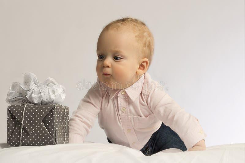 Porträt eines netten Babys mit den großen blauen Augen, die vor seinem Geschenk in eingewickeltem Kasten mit Band liegen Geburtst lizenzfreies stockbild