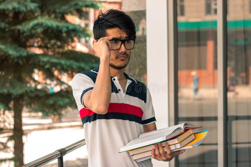Porträt eines netten bezaubernden Studenten in den Gläsern mit Büchern lizenzfreies stockfoto