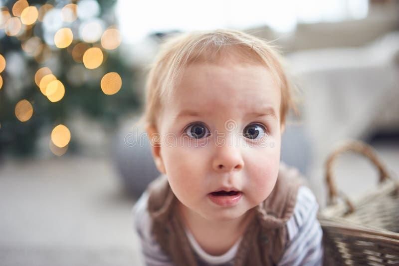 Porträt eines netten einjährigen Babys, das auf dem Boden sitzt Weihnachtsdekorationen auf einem Hintergrund lizenzfreie stockfotos
