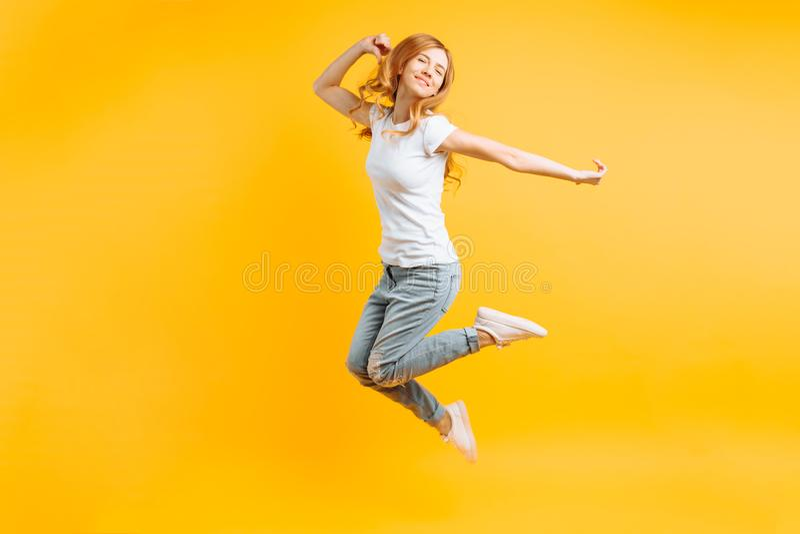 Porträt eines netten enthusiastischen Mädchens in einem weißen T-Shirt, das für Freude auf einem gelben Hintergrund springt lizenzfreies stockfoto