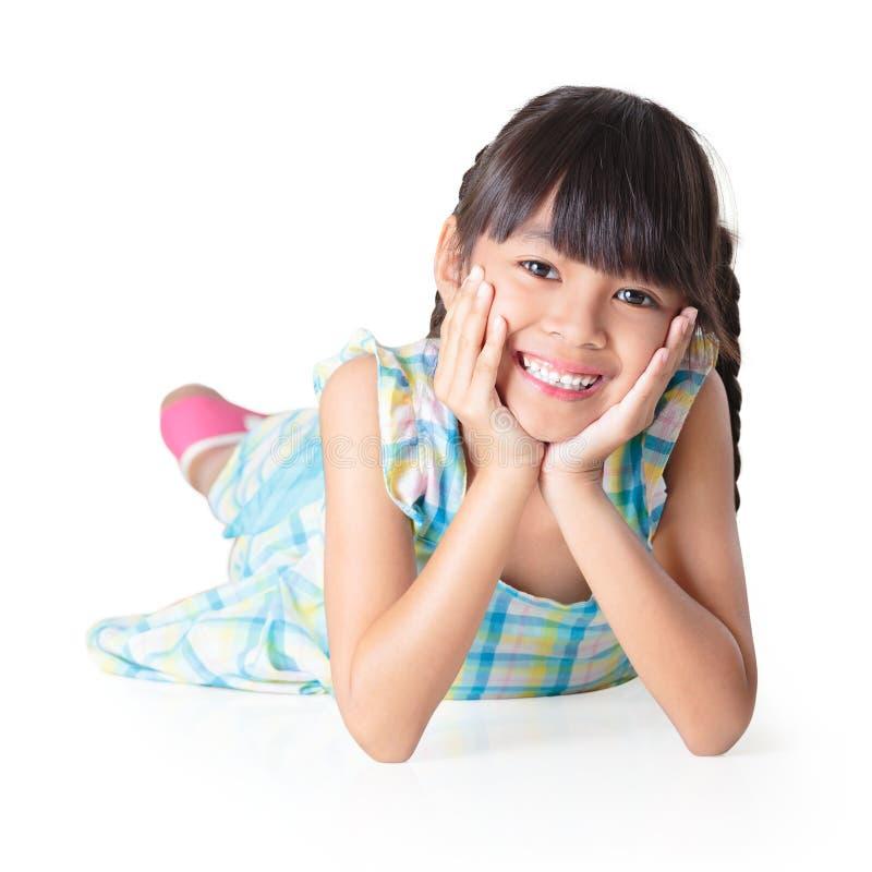 Porträt eines netten glücklichen kleinen asiatischen Mädchens, das auf Boden legt lizenzfreie stockfotografie