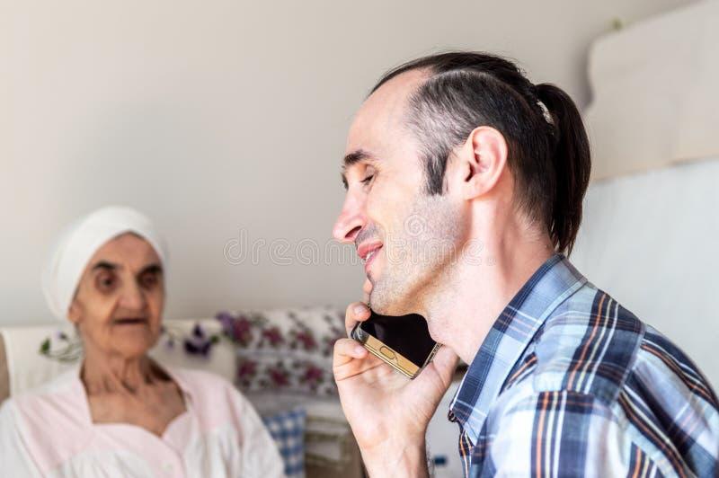 Porträt eines netten, hübschen, kaukasischen Mannes mit stoppeligem Bart sprechend am Handy lizenzfreie stockbilder