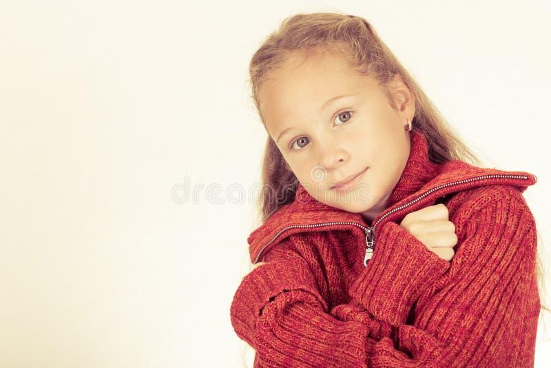 Porträt eines netten jugendlich Mädchens in der roten Strickjacke stockfotos