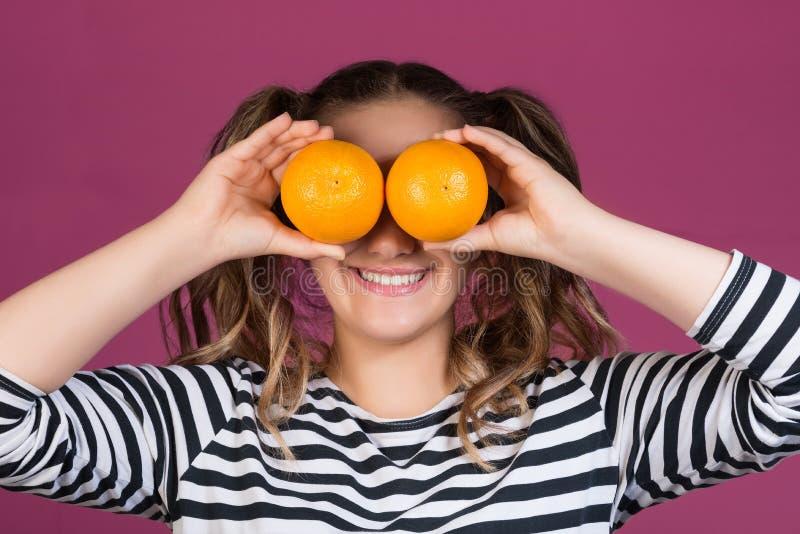 Porträt eines netten jungen Mädchens, das zwei Orangen an ihrem Gesicht hält lizenzfreie stockfotos