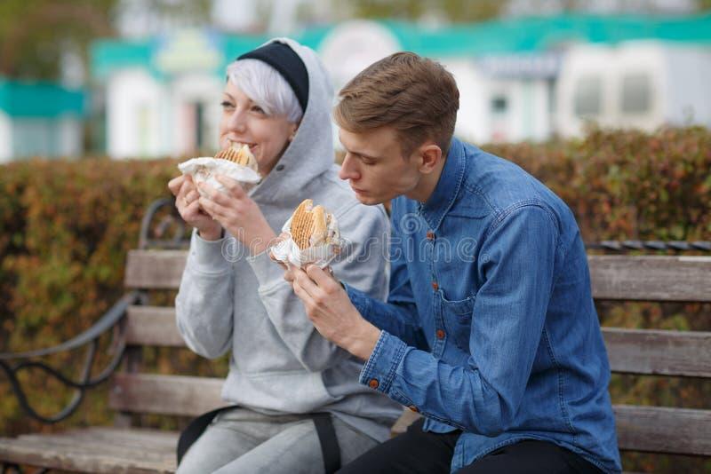 Porträt eines netten jungen Paares, das Burger in einem Park auf einer Bank isst lizenzfreie stockbilder
