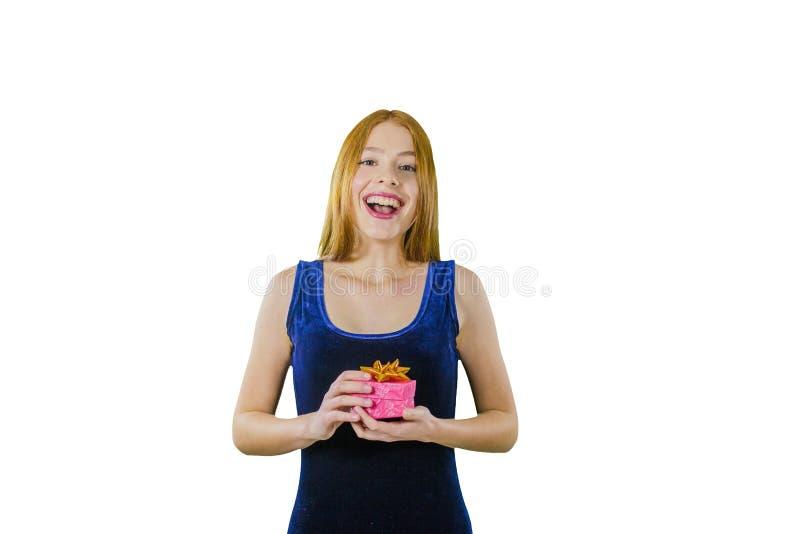 Porträt eines netten jungen rothaarigen Mädchens in einem Glättungskleid mit einem Kasten in ihren Händen emotional lächelnd und  stockfoto