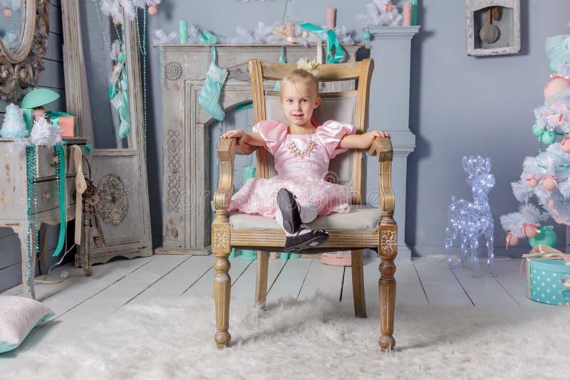 Porträt eines netten kleinen europäischen blonden Prinzessinmädchens in einem schönen Kleid, das auf einem Weinlesestuhl in einem stockfoto