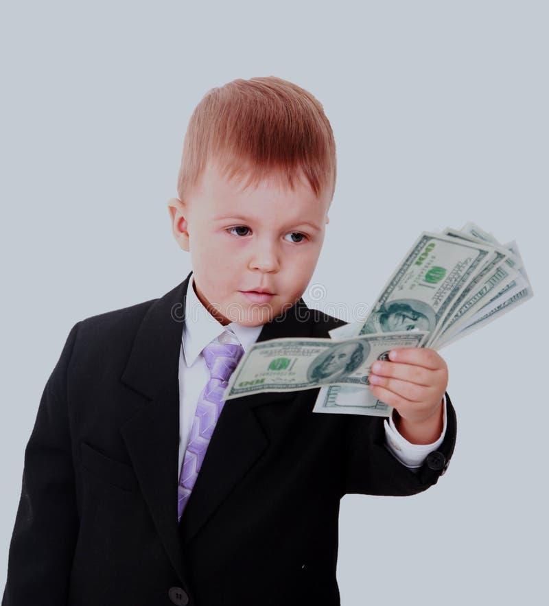 Porträt eines netten kleinen Jungen, der Dollar über weißem Hintergrund hält lizenzfreie stockfotos