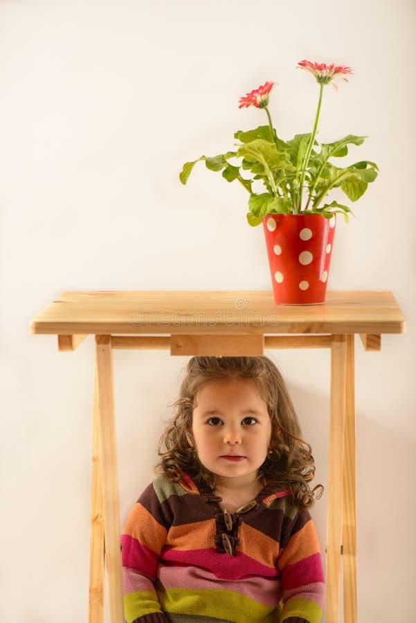 Porträt eines netten kleinen Mädchens, das unter der Tabelle sitzt stockfoto