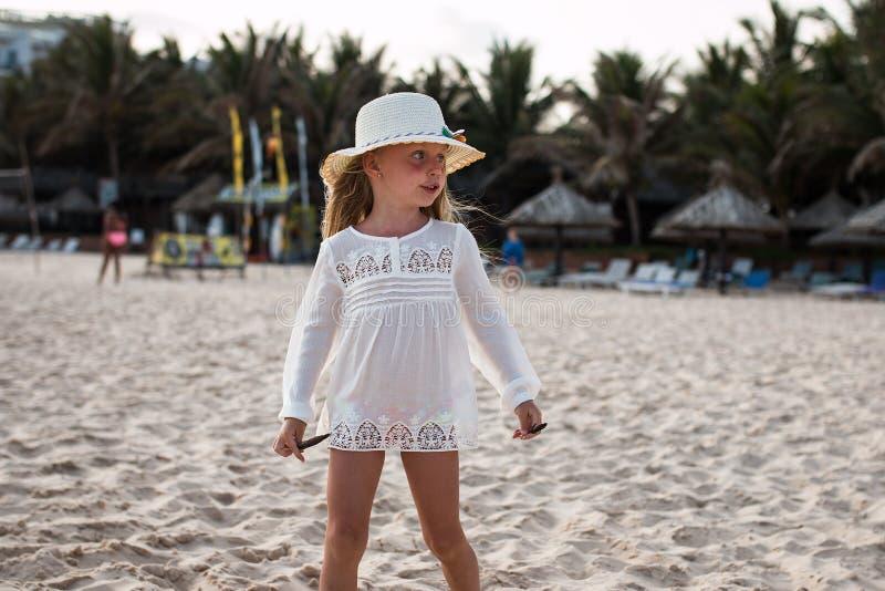 Porträt eines netten kleinen Mädchens in einem Hut auf dem Strand lizenzfreie stockbilder