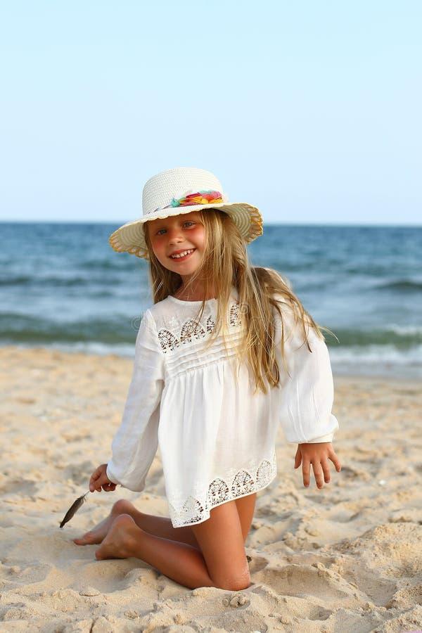Porträt eines netten kleinen Mädchens in einem Hut auf dem Strand stockfoto