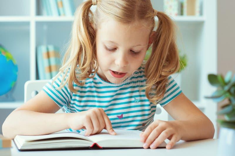 Porträt eines netten kleinen Mädchens las Buch am Tisch im Klassenzimmer lizenzfreies stockbild