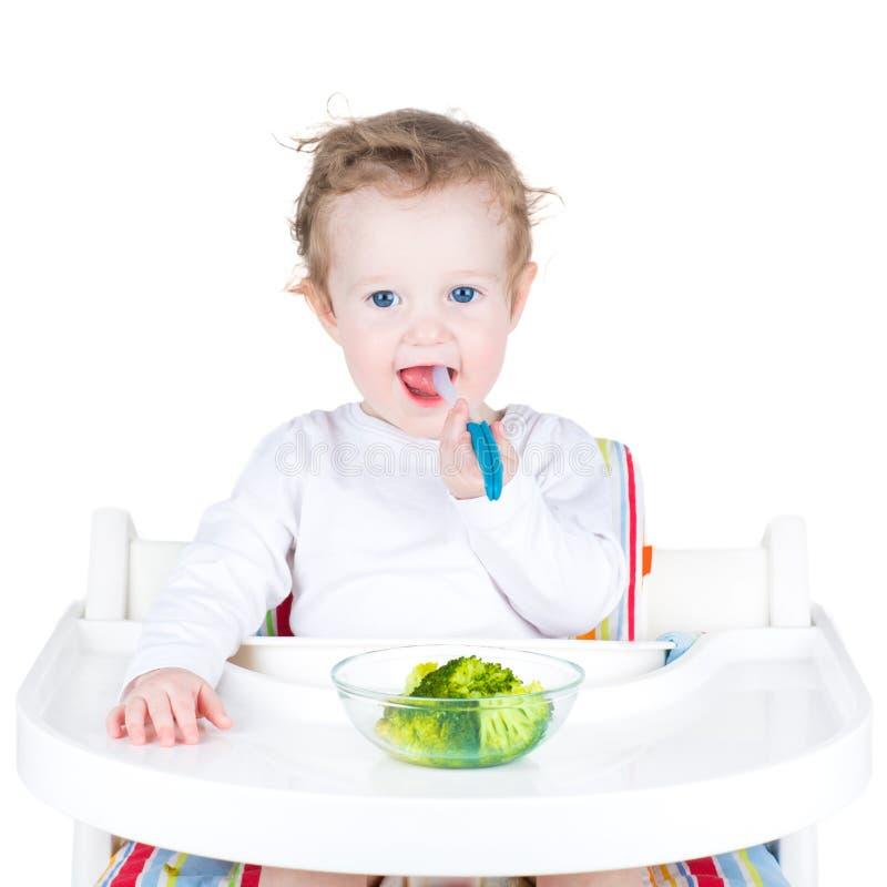 Porträt eines netten Kleinkindes, das Brokkoli in einem weißen Hochstuhl isst stockfotografie