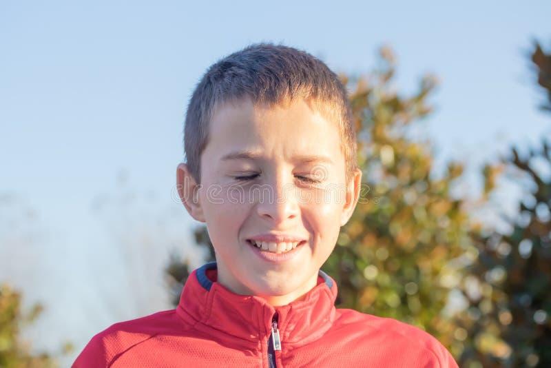 Porträt eines netten lächelnden frohen Jungen mit geschlossenen Augen stockfotografie