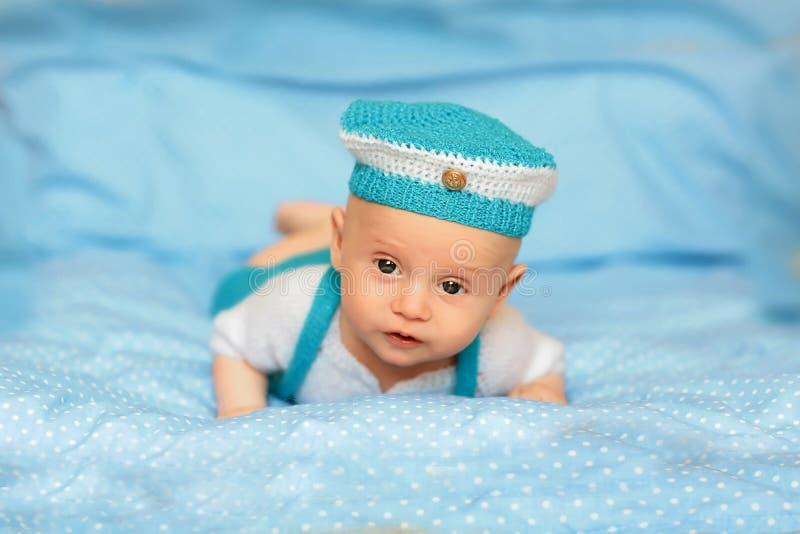 Porträt eines netten 3-Monats-Babys, das sich in einer blauen Klage auf einer Decke hinlegt lizenzfreies stockbild