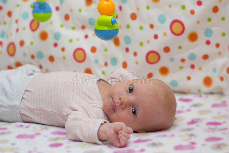 Porträt eines netten neugeborenen Babys, das auf seinem zurück in der Krippe und in den Spielen mit einem Hängen liegt, spielen stockfoto