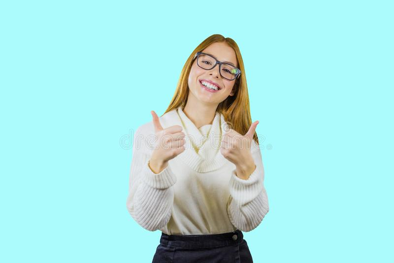 Porträt eines netten rothaarigen Mädchens in den Gläsern und der weißen Strickjacke, welche die Klasse mit beiden Händen lächelnd lizenzfreie stockfotografie