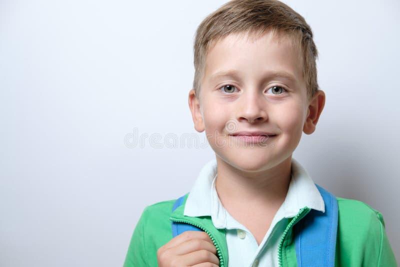 Porträt eines netten Schülers mit blauem Rucksack auf einem weißen backg lizenzfreie stockfotos