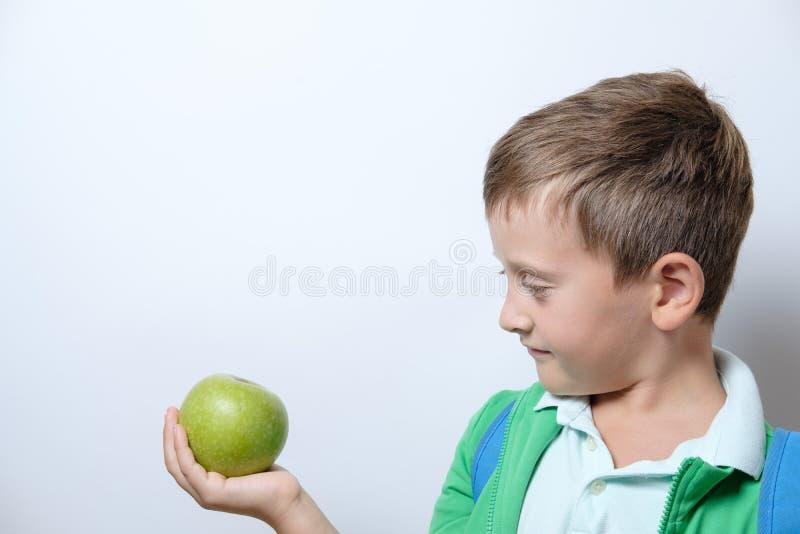 Porträt eines netten Schülers mit blauem Rucksack und grünem Apfel lizenzfreie stockfotografie