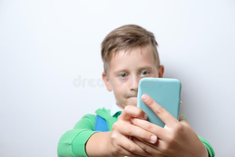 Porträt eines netten Schülers mit blauem Rucksack und intelligentem Telefon stockbilder