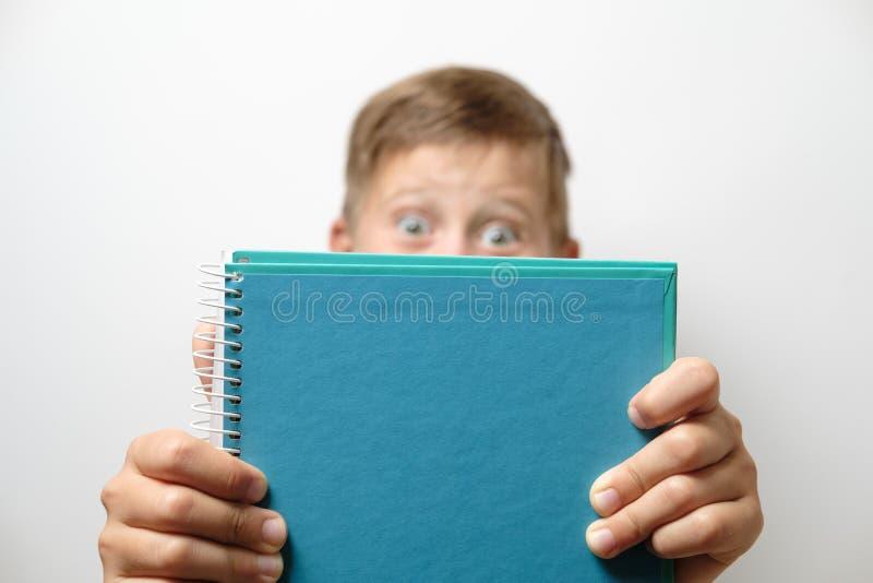 Porträt eines netten Schülers mit blauem Rucksack und Notizbuch an lizenzfreies stockbild