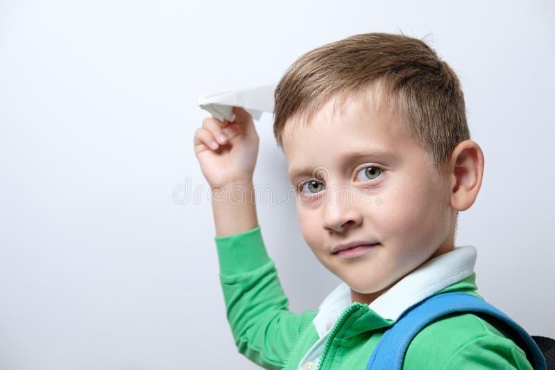 Porträt eines netten Schülers mit blauem Rucksack und Papier airpla lizenzfreies stockbild
