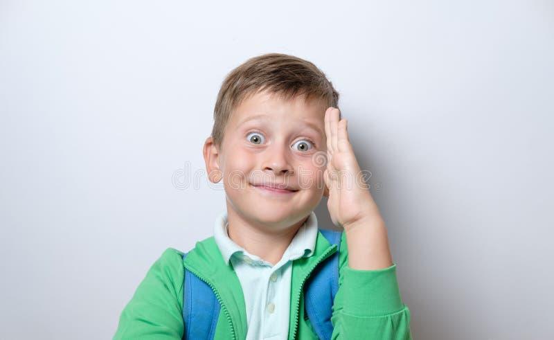 Porträt eines netten Schülers mit blauer Rucksackerhöhung eine Hand an lizenzfreies stockbild