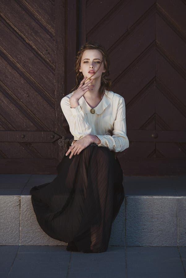 Porträt eines netten träumerischen Mädchens, das draußen Retro- Bluse und Rock trägt Weiches Weinlesetonen stockfotos