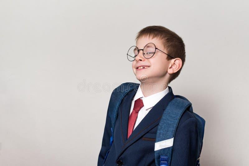 Porträt eines neugierigen Schülers in einer Klage, in den Gläsern und in einem Rucksack Auf schwarzem Hintergrund mit copyspace W stockfotografie