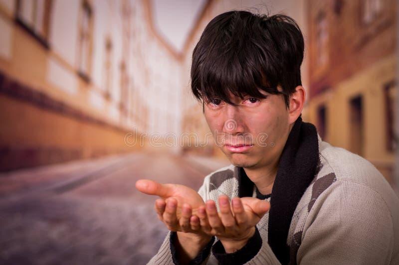Porträt eines obdachlosen jungen Durchschnittsmenschen, bitten um Geld mit beiden Händen, in einem unscharfen Hintergrund lizenzfreie stockfotografie