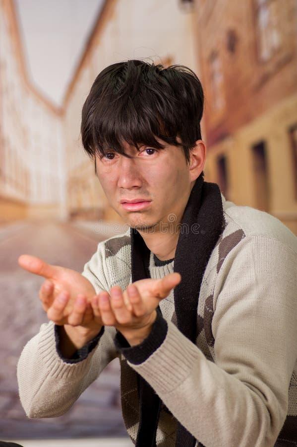 Porträt eines obdachlosen jungen Durchschnittsmenschen, bitten um Geld mit beiden Händen, in einem unscharfen Hintergrund lizenzfreie stockbilder