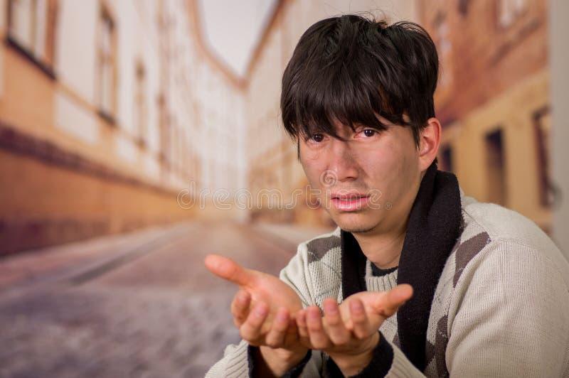 Porträt eines obdachlosen jungen Durchschnittsmenschen, bitten um Geld mit beiden Händen, in einem unscharfen Hintergrund stockfotos