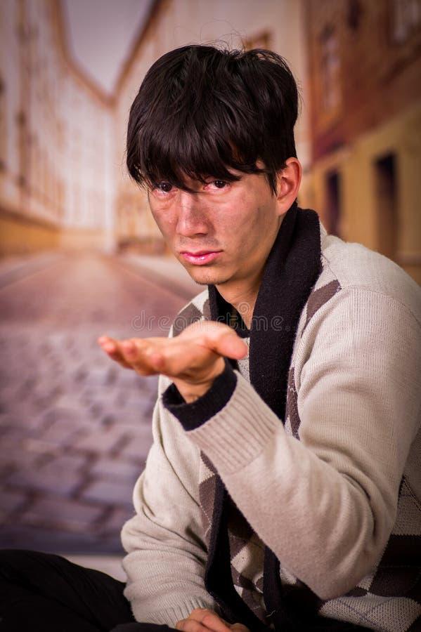 Porträt eines obdachlosen jungen Durchschnittsmenschen, bitten um Geld mit einer Hand, in einem unscharfen Hintergrund stockbild