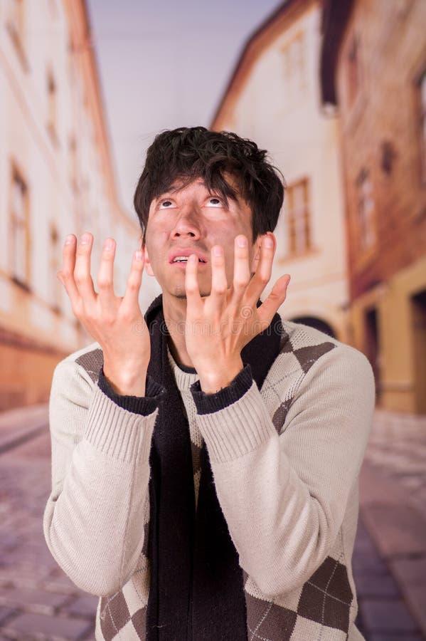 Porträt eines obdachlosen jungen Durchschnittsmenschen, bitten zum Gott um Lebensmittel in einem unscharfen Hintergrund stockfoto