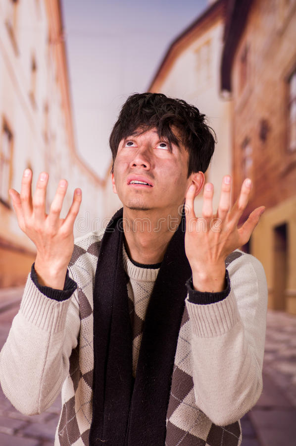 Porträt eines obdachlosen jungen Durchschnittsmenschen, bitten zum Gott um Lebensmittel in einem unscharfen Hintergrund lizenzfreie stockfotografie