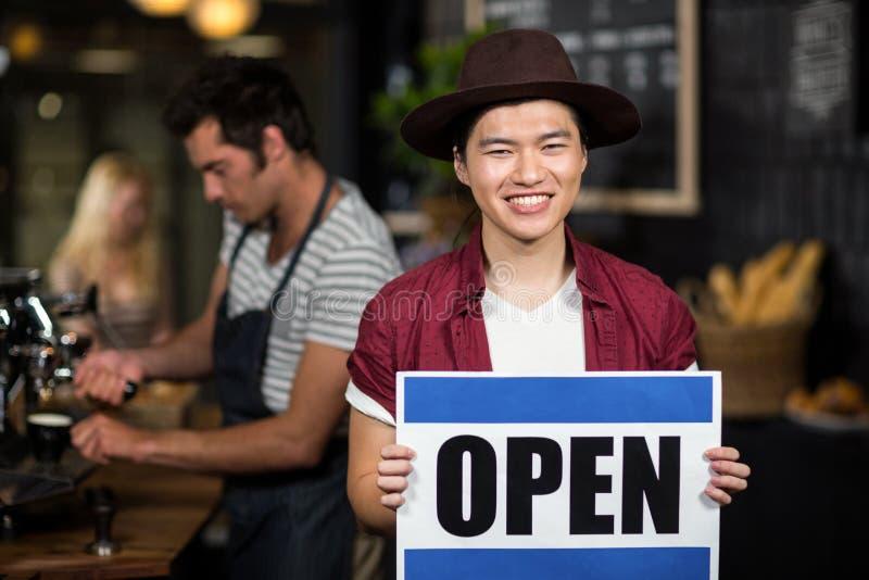 Porträt eines offenen Zeichens der asiatischen Kellnervertretung lizenzfreie stockfotos