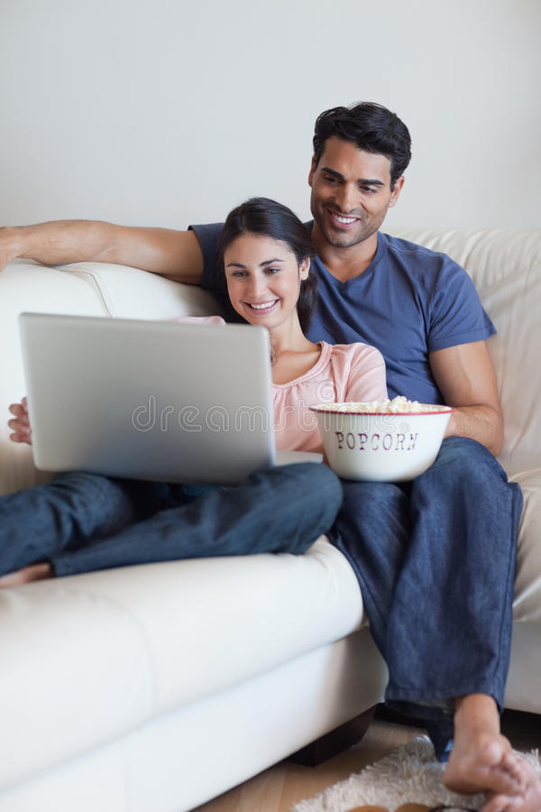 Porträt eines Paares, das einen Film beim Essen des Popcorns überwacht stockfoto