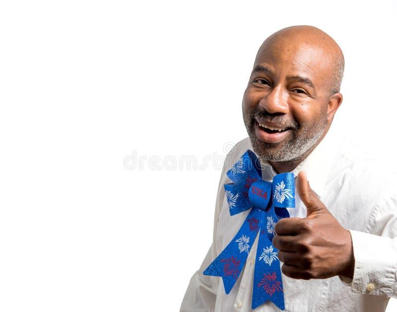 Porträt eines patriotischen Afroamerikanermannes, der Daumen mit Viertel des weißen Hintergrundes Juli-Fliege mit Leerstelle für  lizenzfreie stockfotografie
