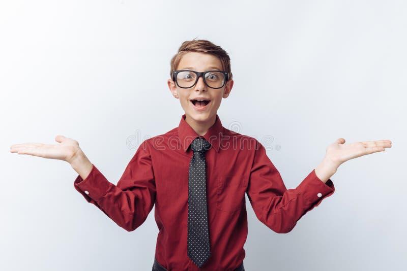 Porträt eines Positivs und überraschter Jugendlicher auf einem weißen Hintergrund, mit Gläsern, rotes Hemd, Werbung, Texteinfügun lizenzfreie stockfotografie