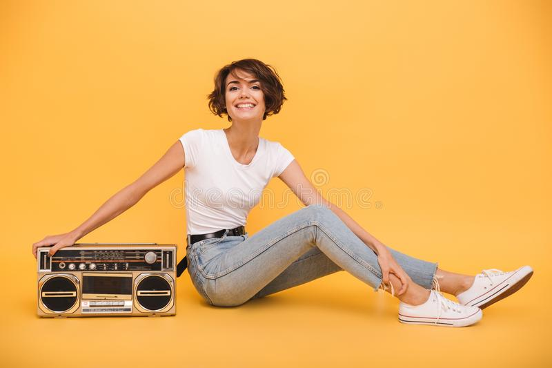 Porträt eines recht frohen Mädchens, das mit Rekordspieler sitzt stockfotografie