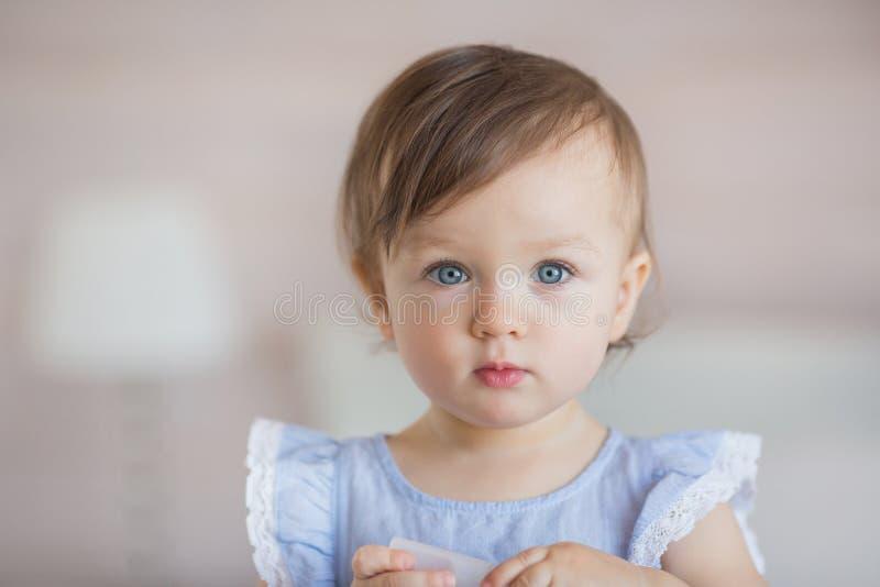 Porträt eines recht kleinen Babys in einem blauen Kleid lizenzfreies stockbild