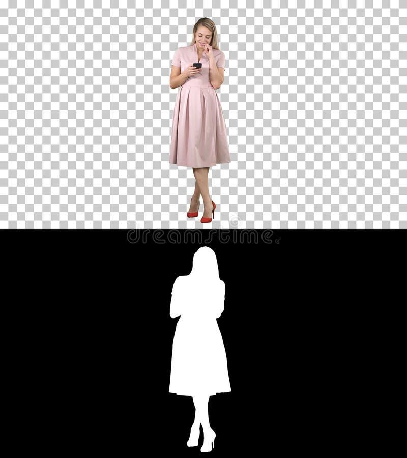 Porträt eines recht lächelnden Mädchens in der Sommerkleidung unter Verwendung des Handys, simsende Mitteilung, Alpha Channel stockfotos