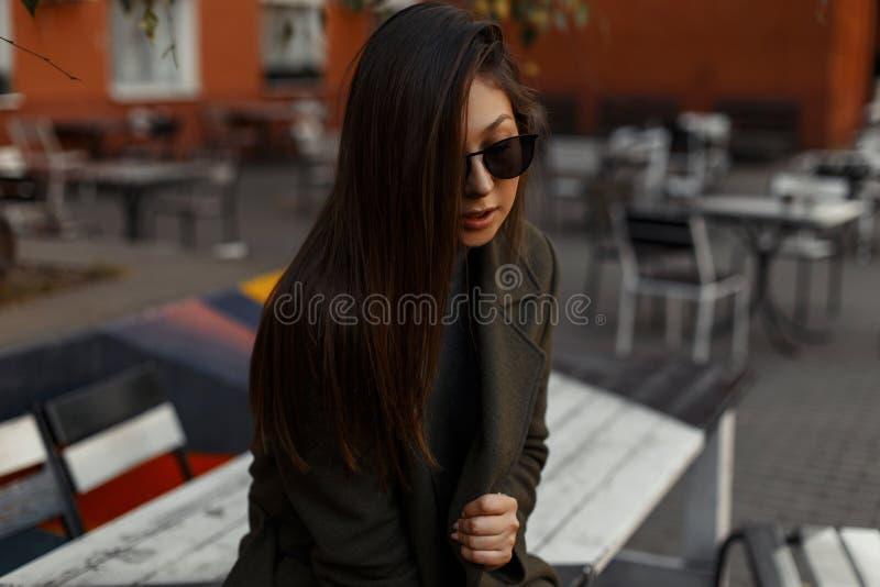 Porträt eines recht schönen und jungen brunette Mädchens in einem stilvollen grünen übergroßen Mantel und in Sonnenbrille, die in stockbilder